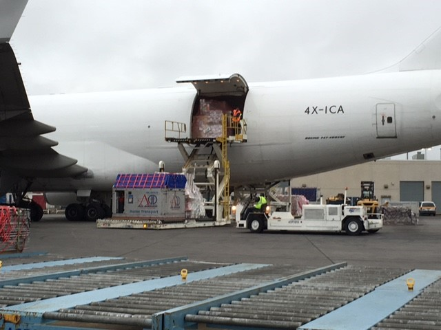 horse box stall being loaded into airplane